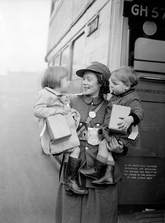 A bus conductress holds two young evacuees who are being taken by bus to a safer part of the country during a London County Council scheme during World War II.