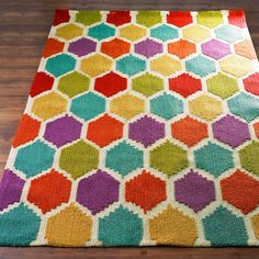 Rainbow Honeycomb Pattern RugCasual elegance and flirty fun combine in this honeycomb pattern rug with a rainbow of color. Hand-hooked in soft polyester with a unique construction combining petit point and bolder loops for intricate high low texture. Rich shades of violet purple, maize yellow, teal aqua, rosey red and peridot green make an eye catching combination against a cream background.