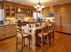 Light wood flooring and beaded inset maple cabinetry create a warm, monochromatic look for this country kitchen. The blues and greens of the backsplash murals and fresh flowers provide lively accents and a natural, woodsy feel.     Designed By: Northeast Cabinet Design  Ridgefield, CT