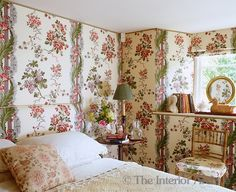 bower-like atmosphere in this bedroom by walls in a large-patterned chintz wallpaper with a Roman blind and headboard to match ~ Somerset, England.