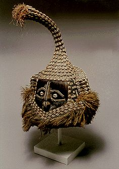 Elephant Mukenga Mask.  Kuba, Zaire.  Made from Cowrie Shells, Beads, Raffia, Fur, Cloth.  The elephant mask, is commonly used among the Kuba, and is worn by a distinguished person during funerary rites of a titled person. The white cowrie shells embellishing this mask are symbolic; white is a color associated with death and mourning. For the Yaka, masks perform in puberty rituals for male youths, as well as assuring and protecting the future fertility of the initiated.