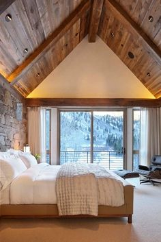 Just steps from the slopes, this Aspen, Colorado, sleeping chamber has a warm, rustic look, with its stone wall and vaulted ceiling.