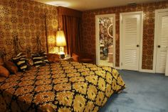 Roz House Bedroom 2: Set of Roz's (played by Jennifer Lawrence) house.  The vintage ranch house had to be completely redone, except for the stone fireplace.  Every inch of the house was covered in vintage foil patterned wallpaper, carpeted, furnished and switched out with vintage appliances as seen in Columbia Pictures' AMERICAN HUSTLE.  Production Design by Judy Becker Photo by:  Alex Linde