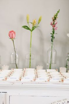escort cards with flowers in bud vases, photo by Tiffany Hughes Photography http://ruffledblog.com/1950s-inspired-auburn-wedding #weddingideas #escortcards