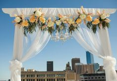 Gorgeous rooftop altar by Emerson Events. Floral by Morrison Floral. Photo by Anna Lee Media. #wedding #altar #yellow #orange #peach #chandelier #draping #rooftop