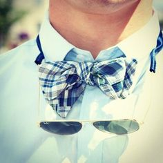 Plaid blue bow tie, Ray Bans, and light blue shirt.