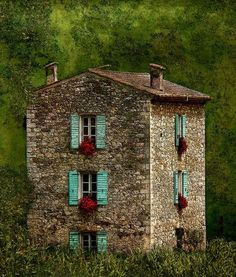 Centuries old stone house with turquoise shutters and flower boxes under each window