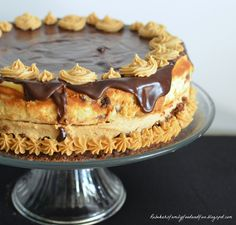 Peanut Butter Cup Brownie Cheesecake dense fudgy brownie followed with a delectable peanut butter frosting, then vanilla cheesecake studded with Reese's peanut butter cups, topped with a rich semi-sweet chocolate ganache and garnished with peanut butter frosting.