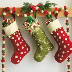 Tips for hanging stockings. My favorite is pictured: via ribbon. Need to buy clear command hooks. Also, I like the Pom garland and it's the colors of our stockings.
