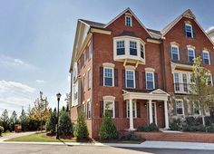 A bay window above a columned entry on the left and a second story balcony above a stone exterior on the right add distinction. The Paces Walk community, John Wieland Homes. Smyrna, GA.