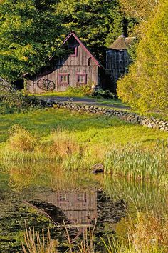 An Old Barn Reflected In The Pond Water