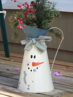 snowman face painted on coffee pot with funnel for hat adored with greenery and berries