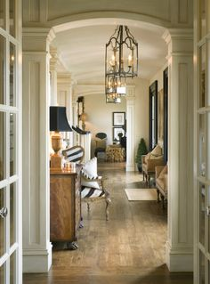 Beautiful hallway with gorgeous moldings framing the doorways, gorgeous furniture and lanterns.