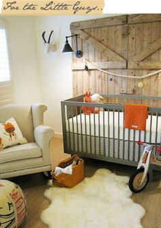 love the texture of the wood barn door, the stag's head, the sisal flooring, grey crib, dark finish on lamps and pop of bright clear color like orange