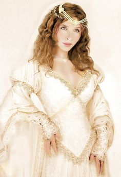 The Faerie Queene has a truly medieval look. It is shown in champagne crushed velvet with gold lace trimmings heavily hand beaded with dainty pearls, fire polished glass beads, and jewel pieces. Champagne hand beaded Baroque lace, and delicate go