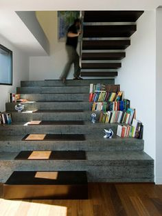 Designed by Castroferro Arquitectos, these extra-wide stone stairs with wood treads on top match the floating wood stairs above, all with enough room to store books on the sides.
