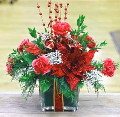 Holiday flowers in a bright red Christmas gift cube decorated with a ribbon, holiday greens, carnations, babies breath and accented with silks. The perfect present!