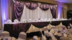 This wedding head table was decked out all the way thanks to the curtains, lights, and flowers.