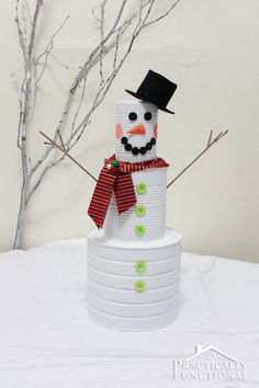 Recycled Tin Can Snowman.. punching a few small holes in it and putting a light or candles in it along your sidewalk would be cute Christmas Eve.
