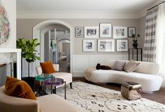 Casual living room with armless white sofa, white patterned rug, wood floors and white and grey walls.