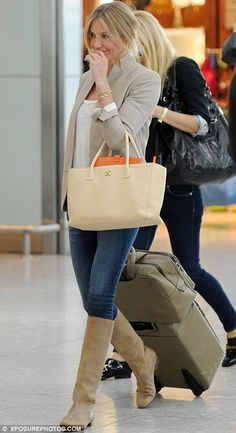 Her outfit is amazing, from the neutral blazer and boots to the peek of orange from her fabulous bag!