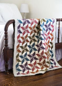Beautiful prints and fun blocks are exactly what quilters love. Designer Janice Averill found this block in a reference book, and chose color values to make the pinwheels stand out. Colorful half-square triangles make up each pinwheel quilt block. A solid border and printed binding complete this fun quilt project.