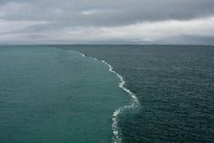 There is a place in the Gulf of Alaska where two oceans meet but do not mix.   This happened because fresh water glaciers melted and flowed to join the ocean water. Because of the difference in the salinity and densities of these two water bodies, a surface tension developed between them that acts like a thin wall which prevents them from mixing.