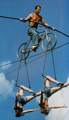 1950s+Man+Shirtless+on+highwire+practice+bicycle+with+two+women+cirucs+performers
