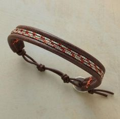Chan Luu threads sterling silver tube beads on rust colored cord between dark brown leather bands. Handmade in USA. Button clasp