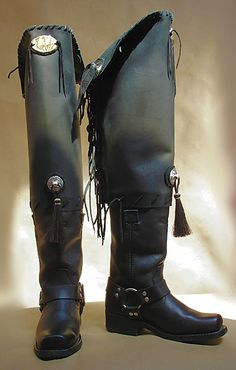 """These """"Ode to Buffalo Bill"""" leather boots by Montana Dreamwear are 25 inches tall and a limited size run. The boots pay tribute to the Wild West show impresario through silver concho embellishments with horse hair tassels, tinkling coins dangling in the back and original Yellowstone Park imagery wood burned on the leather at the top with leather threads"""