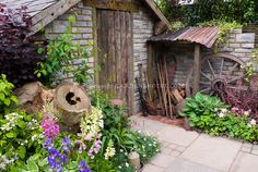 stone garden shed with beautiful flower garden, foliage plants, rustic ...