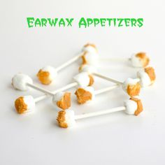 "Before you say ""ewww"", just try one of these earwax appetizers. Take some lollipop sticks and put a mini marshmallow on each end. Dip the ends of the marshmallow in melted butterscotch chips for ooey, gooey earwax bites."
