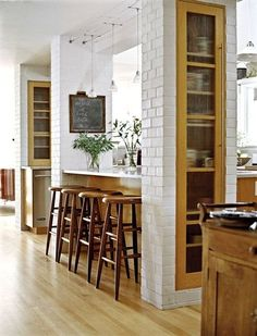 like the brick and the columns with shelving for an open kitchen/living idea