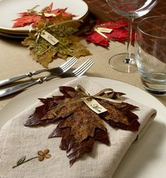Scissor-cut maple leaves out of leather or fabric for simple and elegant Thanksgiving place settings!