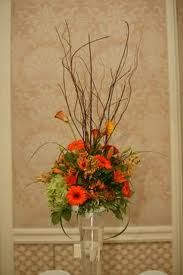 Picturing something similar to this for the taller arrangements - not as dense at the base, but with branches for height and colorful flowers at the bottom