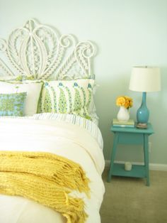 i love this color scheme. i love the turquoise blue, yellow, green and white combination. the headboard is beautiful. i love the pillows, the yellow throw, the end table, the lamp and the flower vase.