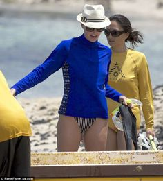 Fun in the sun: She kept sun safe in a trilby straw hat while covering her eyes with large dark sunglasses and Coolibar Long Sleeve Swim Shirt.