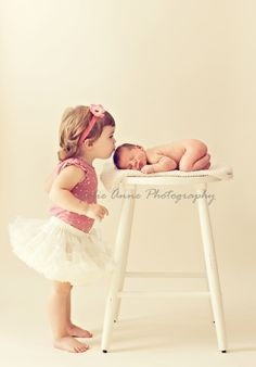 sibling kisses newborn photo