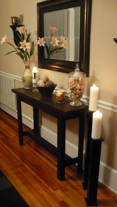 console table decor. Love the pillar candle stands!