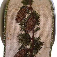 """Burlap Embroidered Ribbon Size: 4"""" in width; 5 yards in length Color: Natural, Dark Green, Brown Wire Edge 100% Jute Beautiful clusters of single and double pinecones and greenery"""
