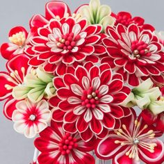 A red tsumami kanzashi hair piece. Looks like mums, freesia, cherry or plum blossoms and dahlias are represented here.