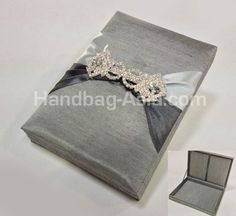 Silver Look Silk Wedding Invitation Box. For every bride and groom that loves a bit of a bling bling. This silk box was designed in a silver theme with large rhinestone crystal brooch. Padded interior and exterior, pockets for RSVP and invitation cards. Comes in all imaginable colors and sizes.