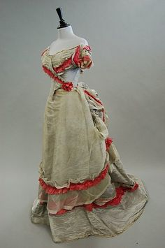 A grey moire taffeta ball gown trimmed with pink  Sign In to see what this sold for  A grey moire taffeta ball gown trimmed with pink silk, circa 1870, with pointed front bodice, the polonaised skirt draped and cascading from the back, (2)      Condition report  apron-like over skirt which is made of grey organza is very frayed and torn, brown water marks to moire skirt which is revealed below