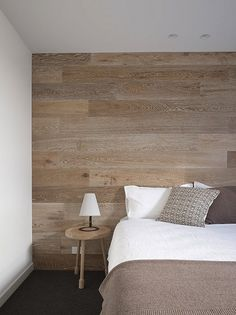 Royal Oak Wooden Wall Decor. This rustic wood wall feels contemporary in this minimalist bedroom. The simple colors and linear lines of the wall are in keeping with the contemporary style of the rest of the room.