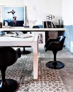 I love the idea of one wall-to-wall cantilevered work shelf, and a floating island desk. I am loving the black, curvy Saarinen chairs paired up with the white rectilinear table. The rough cement floor says that this is a no-nonsense space. The colourful artwork leaning against the shelf adds vibrancy... as does the blue painterly marks on the right wall.