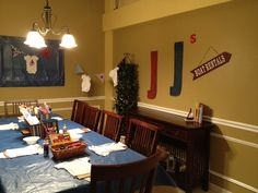 Onesie decorating room. Craft set-up on table with supplies. Onesies strung on twine throughout room mixed with 'nautical' pennants.  Simple thrift store decor on walls.
