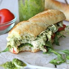 Chicken pesto sandwich on a freshly baked baguette with arugula, tomato, and thick mozzarella slices.