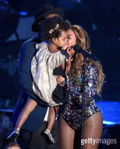 Recording artist Jay-Z (behind, wearing hat) and daughter Blue Ivy Carter (C) present the Michael Jackson Video Vanguard Award to honoree Beyonce (R) onstage during the 2014 MTV Video Music Awards at The Forum on August 24, 2014 in Inglewood, California.  (Photo by Michael Buckner/Getty Images)