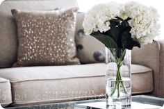 lovely white hydrangeas, shimmery pillow, neutral sofa. classic and gorgeous.