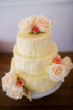 Three-tiered buttercream wedding cake with pink roses.